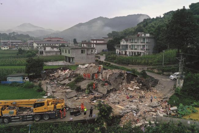 Rescue workers search for trapped people at a collapsed building after an earthquake in Shuanghe Town in Changning County of Yibin City