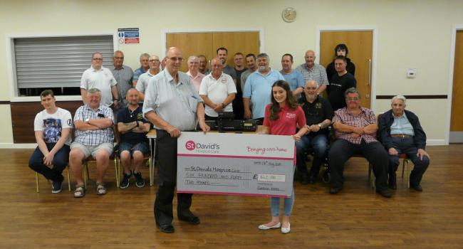 Skye Lewis, of St David's Hospice Care, receives a cheque for £642 from Cwmbran and District Amateur Radio Society at Henllys Village Hall. Picture: DBPR