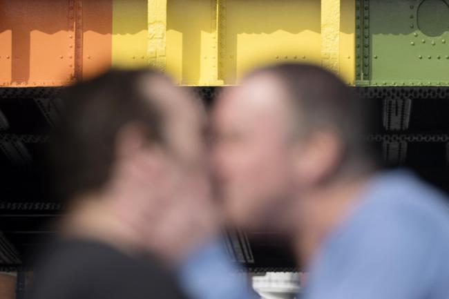 Two men kiss in front of a rainbow coloured bridge