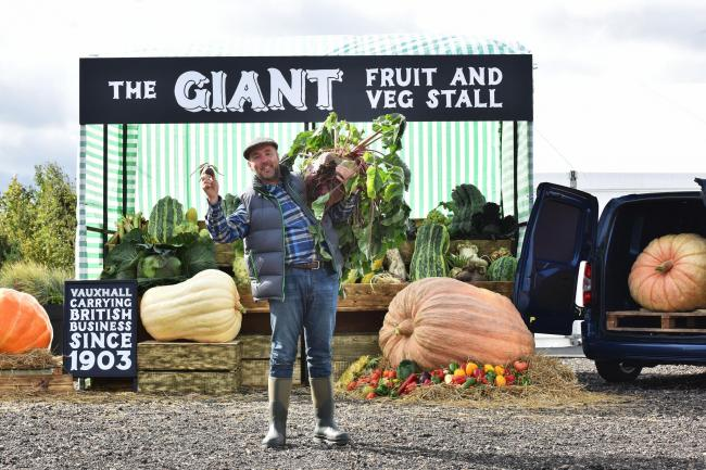 FREE TO USE IMAGES  Pictured: Giant veg grower Kevin Fortey next to the stall.  Vauxhall have created a 'giant fruit and veg stall' to demonstrate there is no job too big for the UK's small businesses, and have partnered with champion veg grow