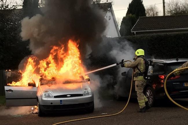 A SWFRS firefighter tackles a car fire in Greenmeadow, Cwmbran. Picture: SWFRS/Twitter