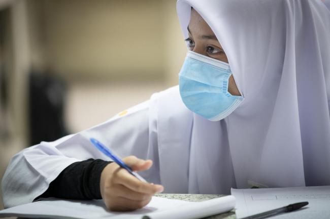 A student wearing a face mask takes a class during the first day of school reopening at a high school in Putrajaya, Malaysia, Wednesday, June 24, 2020. Malaysia began reopening schools Wednesday while entering the Recovery Movement Control Order (RMCO) af
