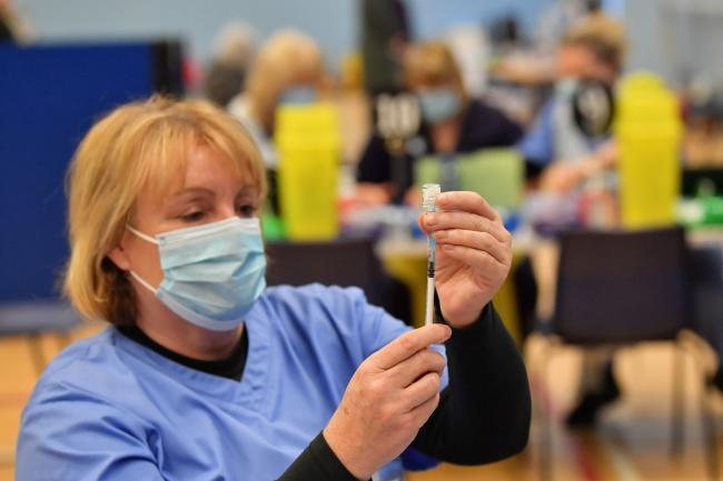 Health care workers give out injections of the Pfizer vaccine at a coronavirus vaccination centre set up at Cwmbran Stadium, south Wales. Picture date: Tuesday January 26, 2021.