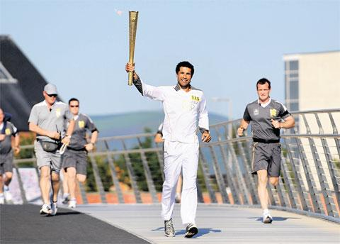 HONOUR: Richard Parks carries the Olympic Torch in Swansea on Saturday