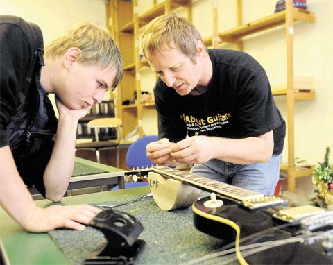 GUITAR MAN: Kevin Webb helps Troy Cousins, from Newport, repair an instrument in oneof his guitar workshops