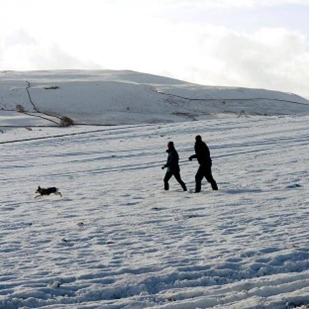 Walkers in the snow as they cross Middleham Moor in The Pennines