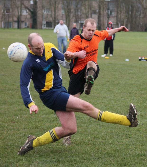 Mathern Wanderers' hat-trick hero Sammy Davies (orange shirt) outwits a Sudbrook CC defender.