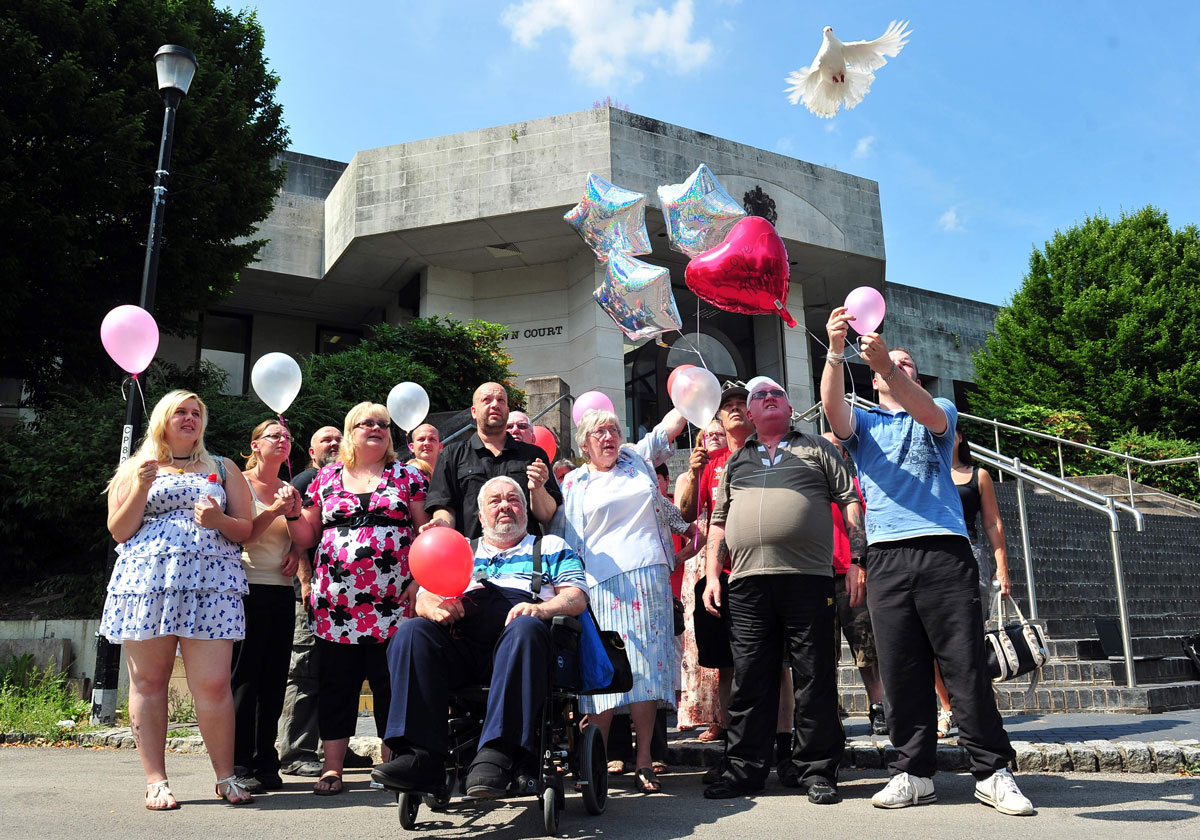 TEARS: Family members look on at the end of the trial as the balloons and doves are released