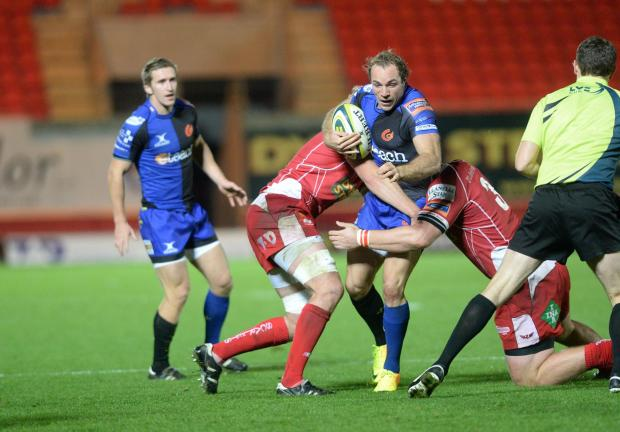 Free Press Series: Scarlets v Dragons 081113 Will Harries is tackled by two Scarlets players. (2393057)