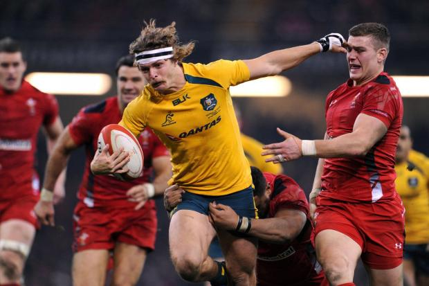 GREAT SCOTT! Australia's Nick Cummins hands off Wales' Scott Williams