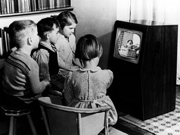 DECLINE:  Children gathered around a black and white television set watching children's show, Andy Pandy, first shown in 1950. ©BBC