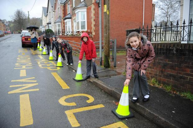 Children from George Street Primary School under the guidance of Head Teacher Julie Wood launched the school's green cone scheme to stop parents parking illegally.  Pictured front is Jessica Parfitt aged 9 from year 5 placing a cone on the road. (3404