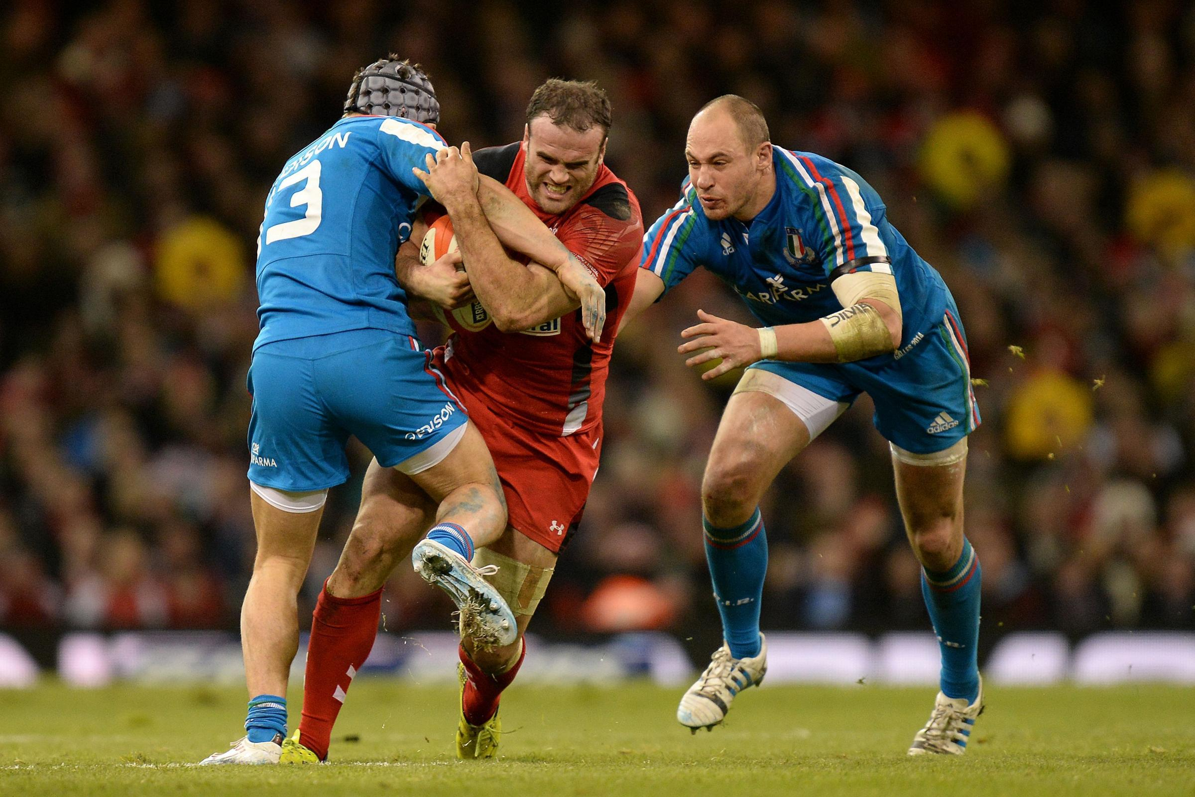 Wales' Jamie Roberts (centre) runs away from Italy's Sergio Parisse (right) into a tackle from Italy's Michele Campagnaro (left) during the RBS 6 Nations match at the Millennium Stadium, Cardiff. PRESS ASSOCIATION Photo. Picture date: Saturday