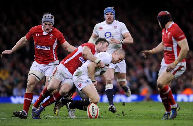 England's Mike Brown (centre right) fumbles the ball as he is tackled by Wales Alex Cuthbert (centre left) during the RBS Six Nations match at the Millennium Stadium, Cardiff. PRESS ASSOCIATION Photo. Picture date: Saturday March 16, 2013. See PA stor