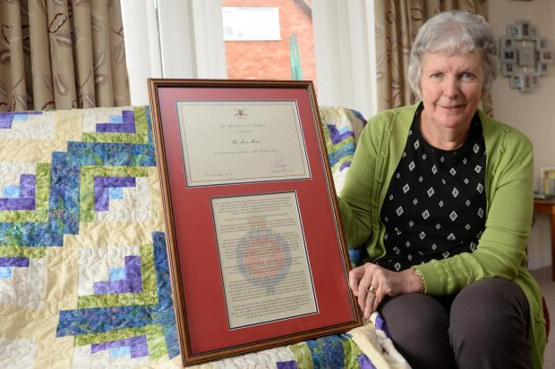 Jean Morris of Monmouth has been awarded a military honour after sending almost 1000 hand made quilts to injured soldiers. Pictured is Jean at home in Monmouth with her award and an example of one of her quilts. (4503366)