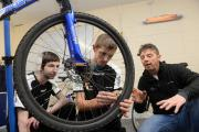 WHEELS: Rob Barr checking the spokes along with Brandon Miller and Stephen James from Changing Gearz.