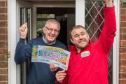 CELEBRATING: People's Postcode Lottery winner Mike Burden receives his winning cheque from ex-Wales rugby star Scott Quinnell