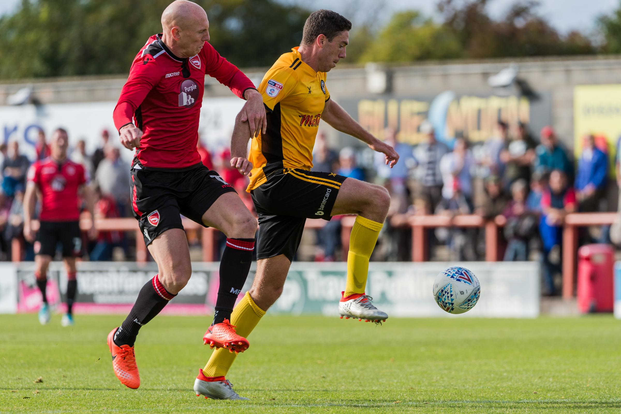 BATTLE: Newport County's Ben Tozer tussles with Morecambe match-winner Kevin Ellison last Saturday. Picture: Huw Evans Agency