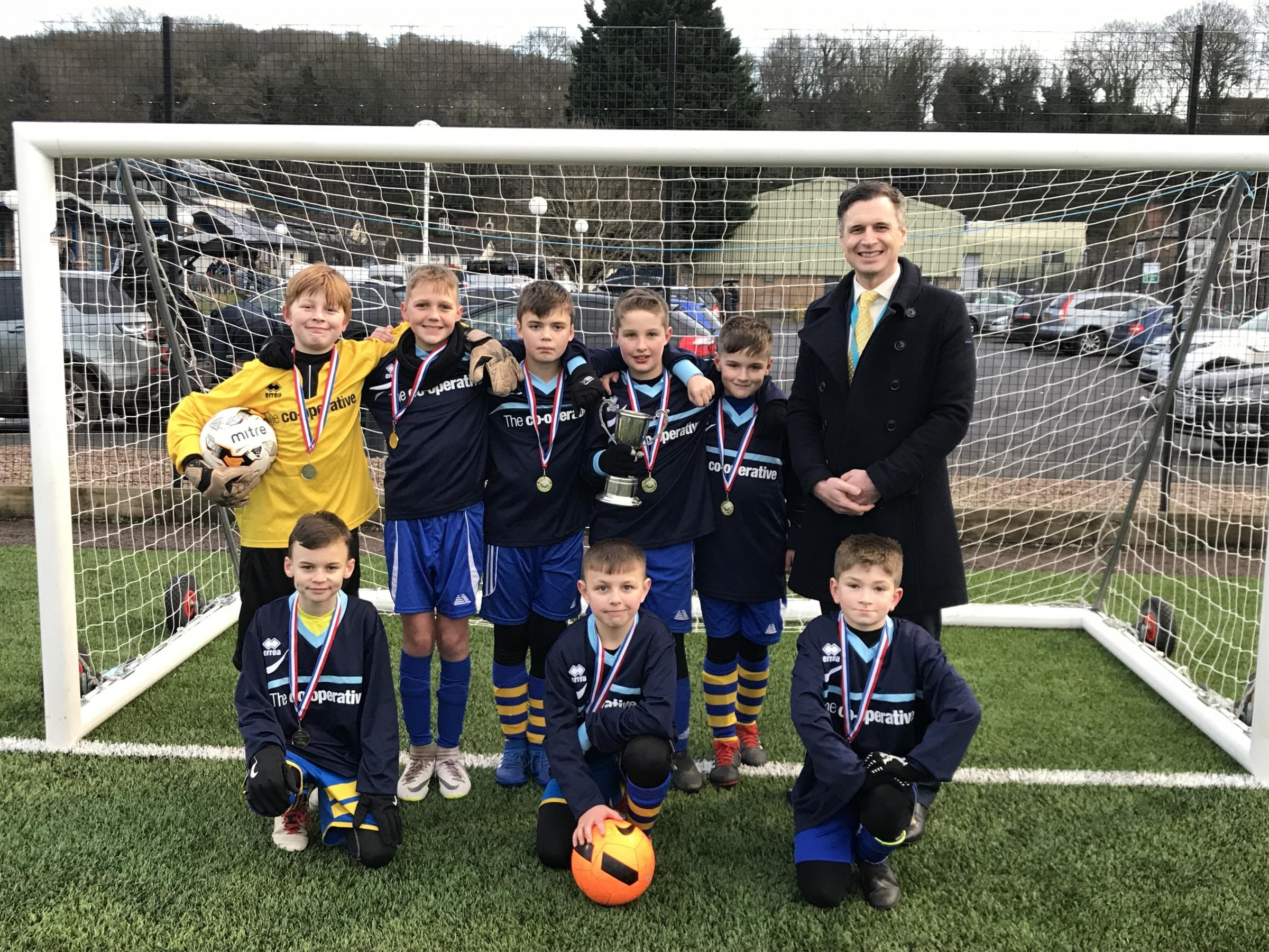 Overmonnow Primary School's A-team after being presented with the cup by Neil Shaw, headteacher at Monmouth School Boys' Prep.