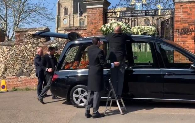 Free Press Series: Flowers being placed in and on the hearse