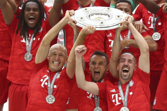 Arjen Robben, front left, and Franck Ribery, front right, lift the trophy to celebrate Bayern's seventh straight Bundesliga title